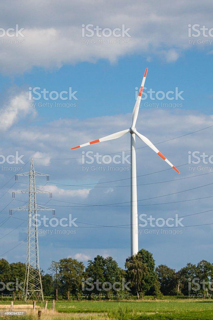 Windrad neben Hochspannungsmast stock photo