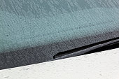 Windshield Bonett and Wiper Arm Covered in Water Droplets