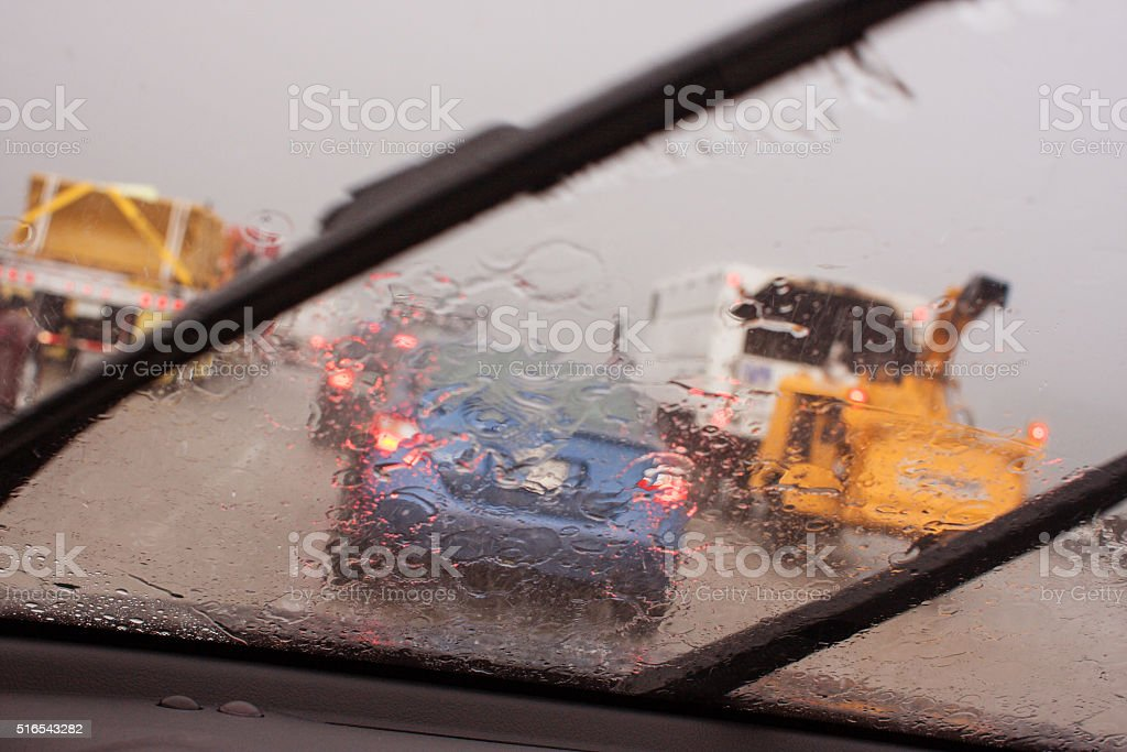 POV Windshield Wipers Displacing Heavy Rain In Rush Hour Traffic stock photo