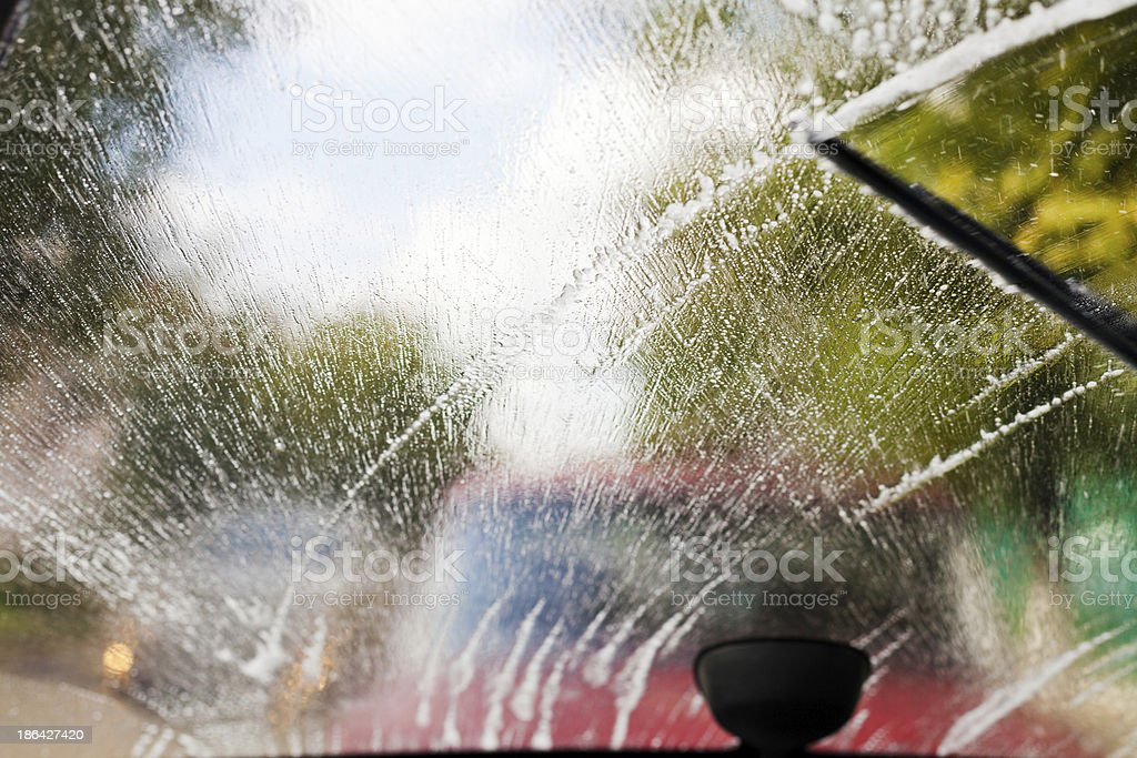 Windshields wipers wiping away rain from windshield of car royalty-free stock photo
