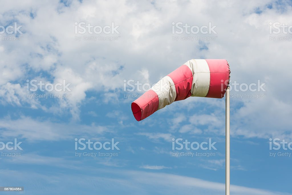 Windsock blowing in wind against cloudy sky stock photo