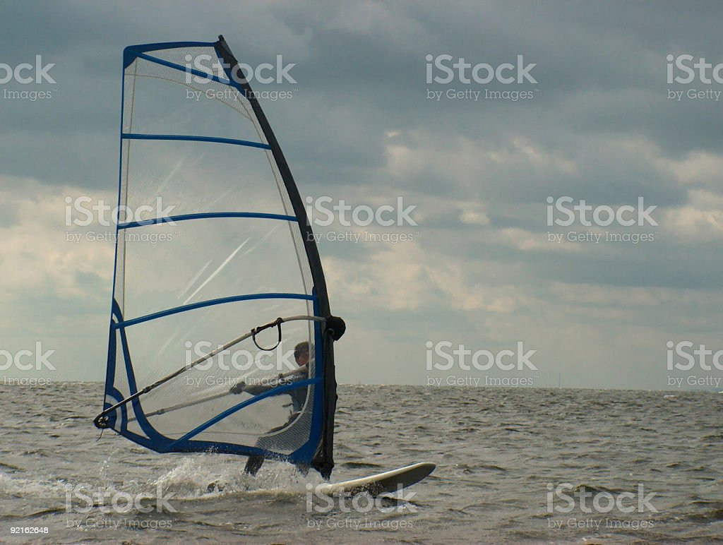 Windsurfer on a cloudy day stock photo
