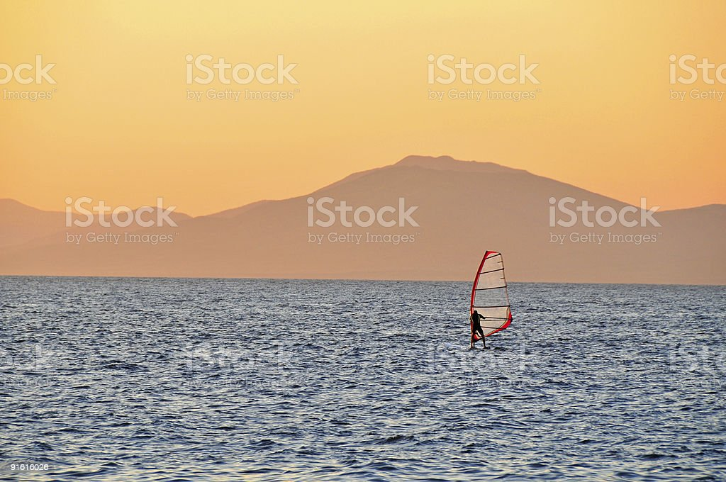 windsurfer sailing on a sunset stock photo