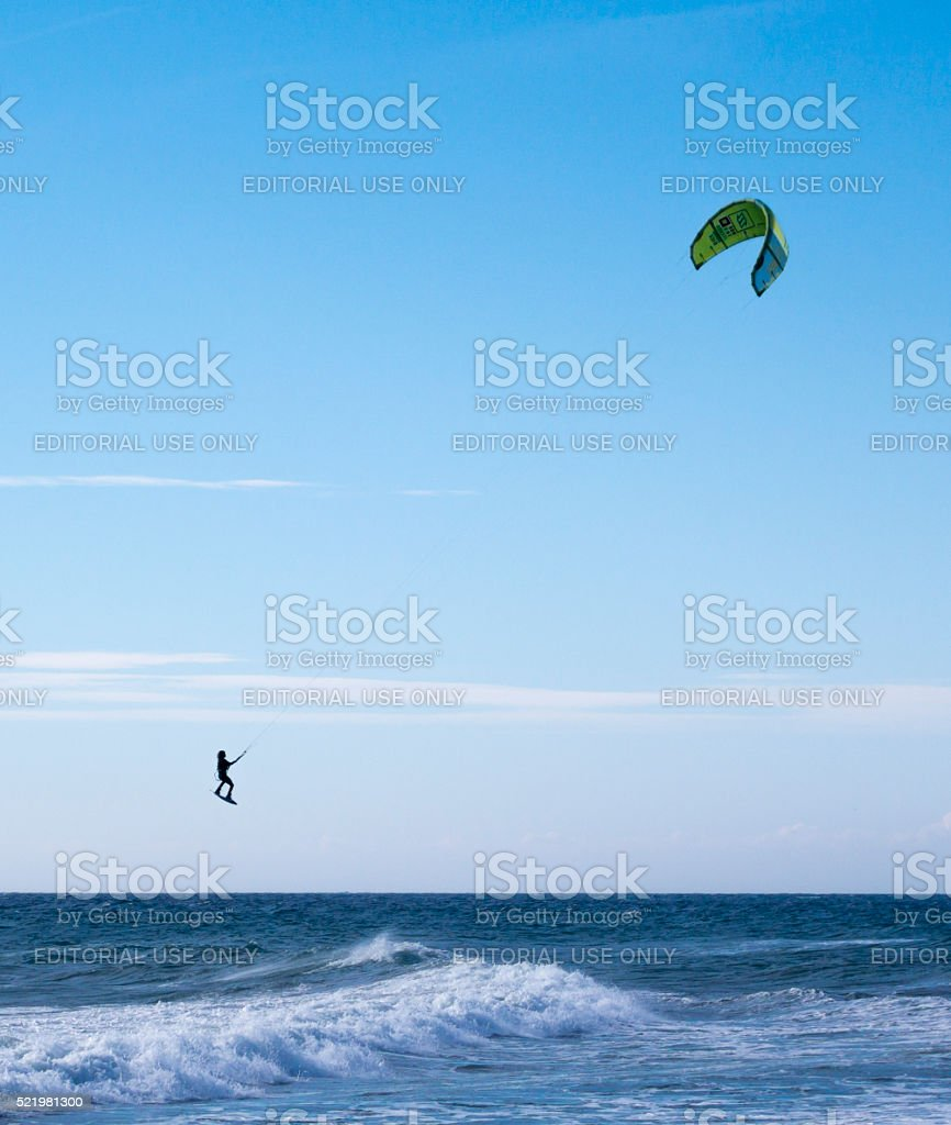 Windsurfer taking off in Nerja on a sunny windy day stock photo