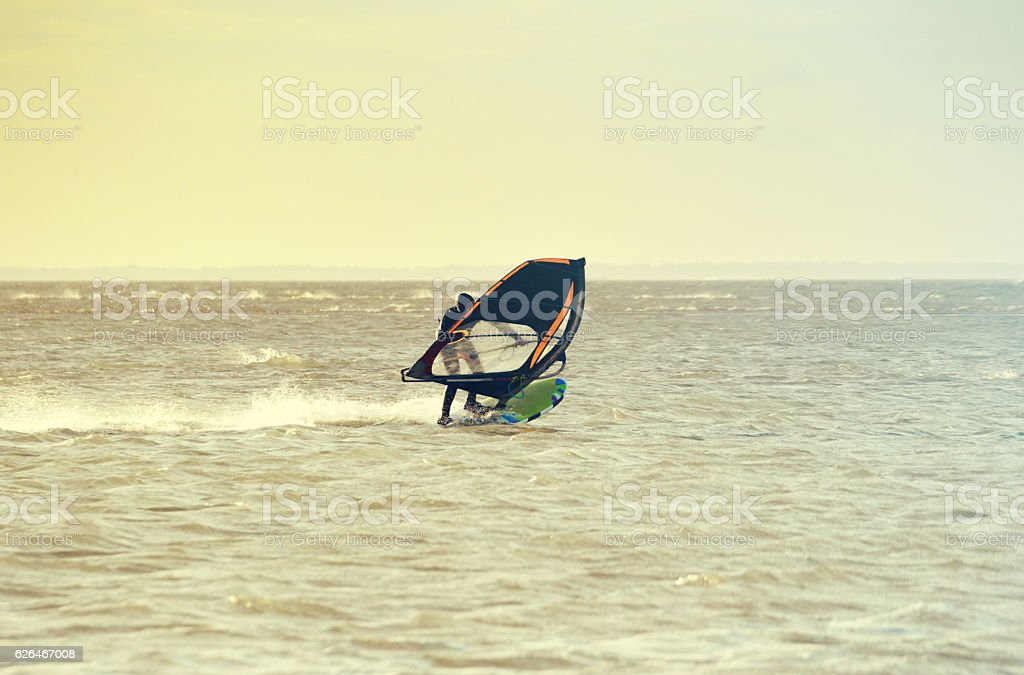 Windsurfer with sail ducked stock photo