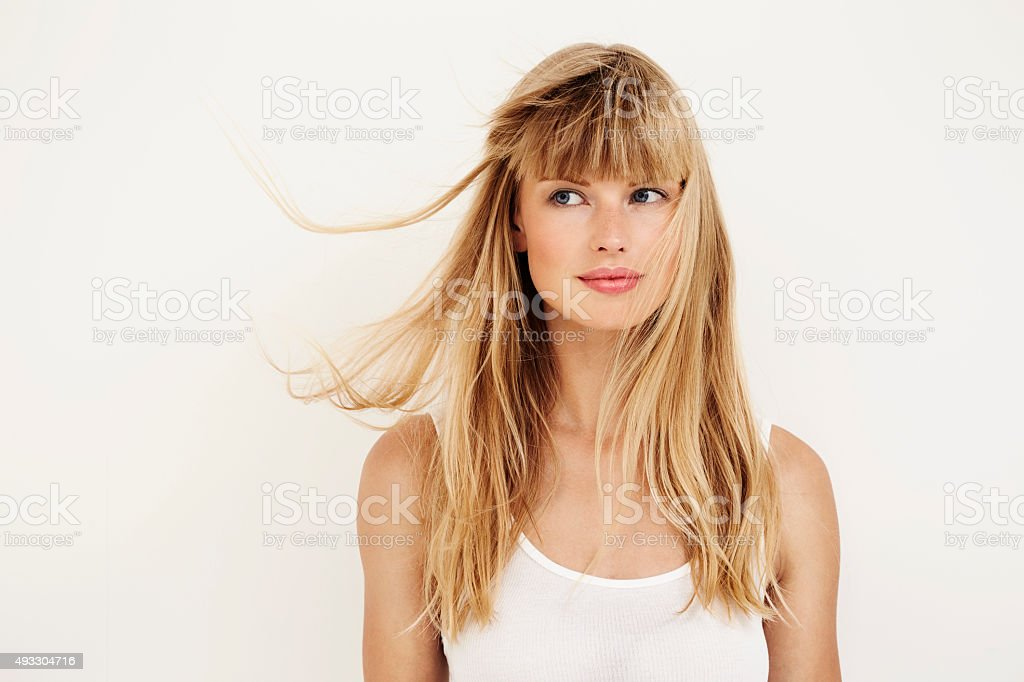 Windswept young woman with blond hair stock photo