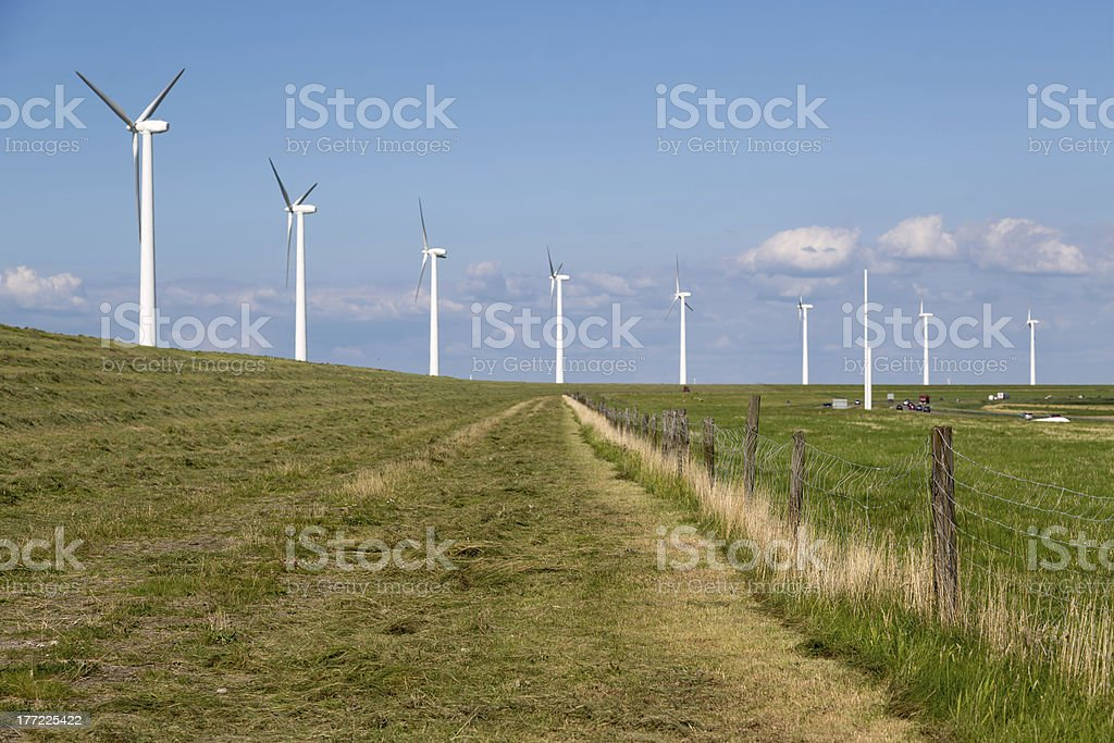 Windturbines along a dike in the Netherlands near motorway royalty-free stock photo