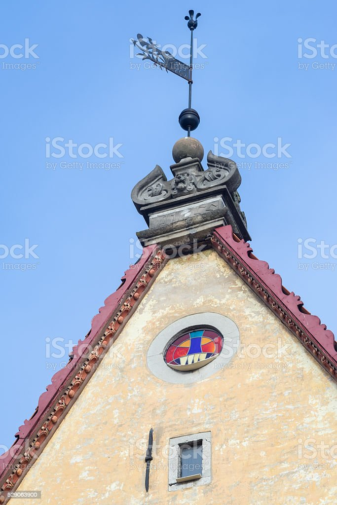 Wind-vane on roof top of medieval house stock photo
