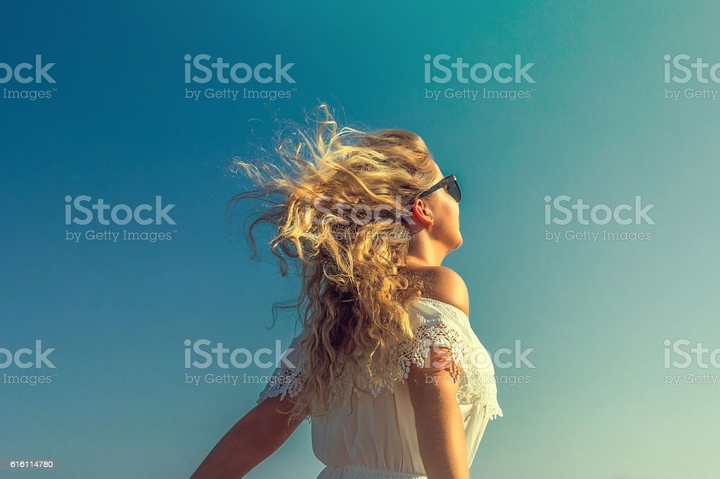 windy in hair dreamy girl with sunflare on beach stock photo