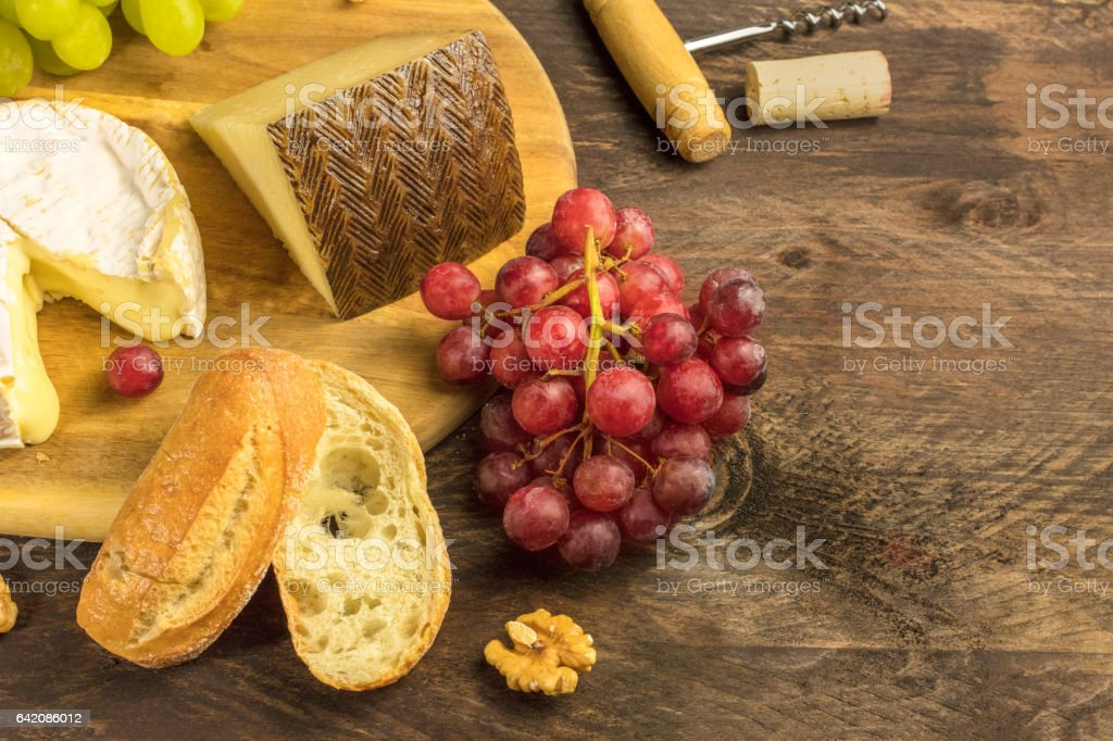 Wine and cheese tasting with bread, grapes and cork stock photo