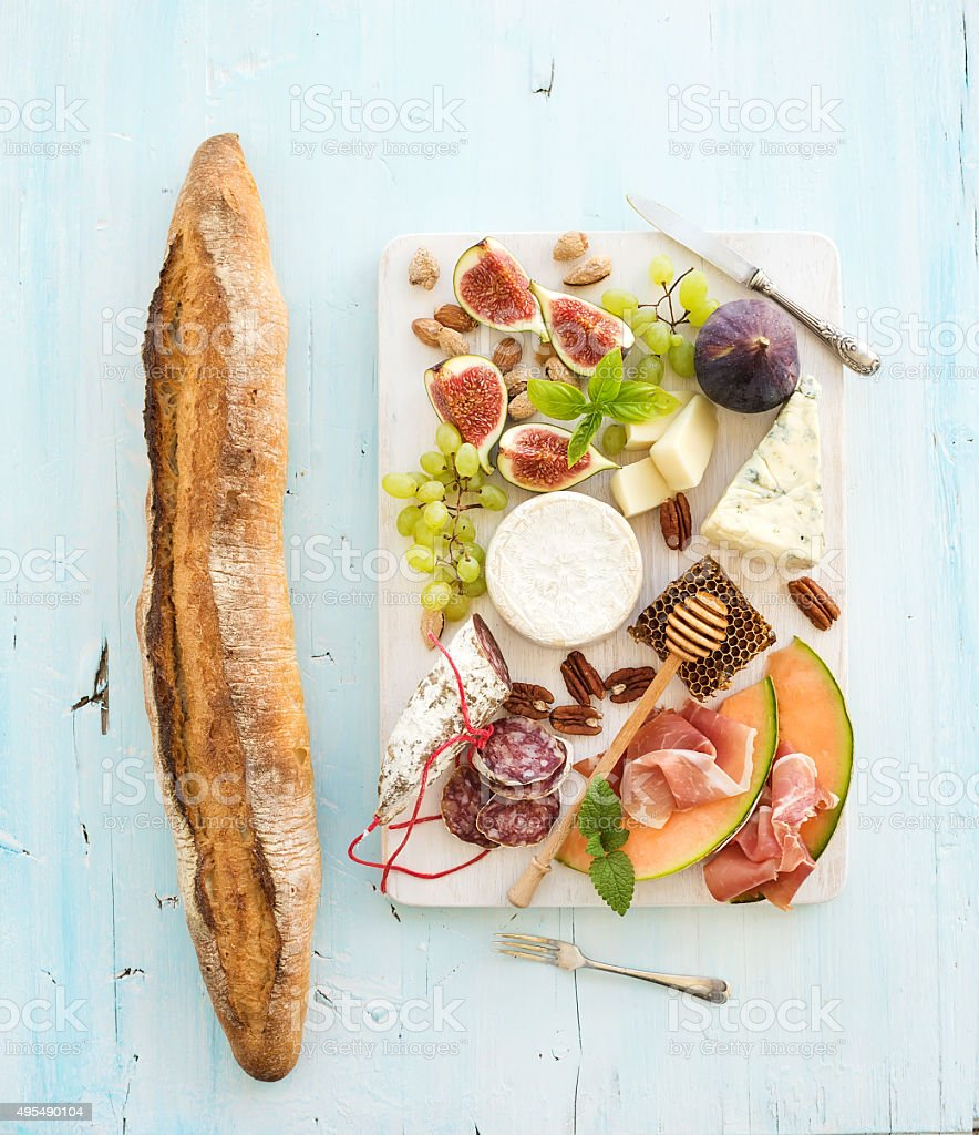 Wine and snack set. Baguette, figs, grapes, nuts, cheese variety stock photo