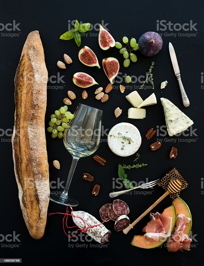 Wine and snack set. Baguette, glass of white, figs, grapes stock photo