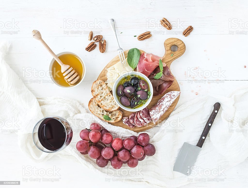 Wine appetizer set. Glass of red, grapes, parmesan cheese, meat stock photo