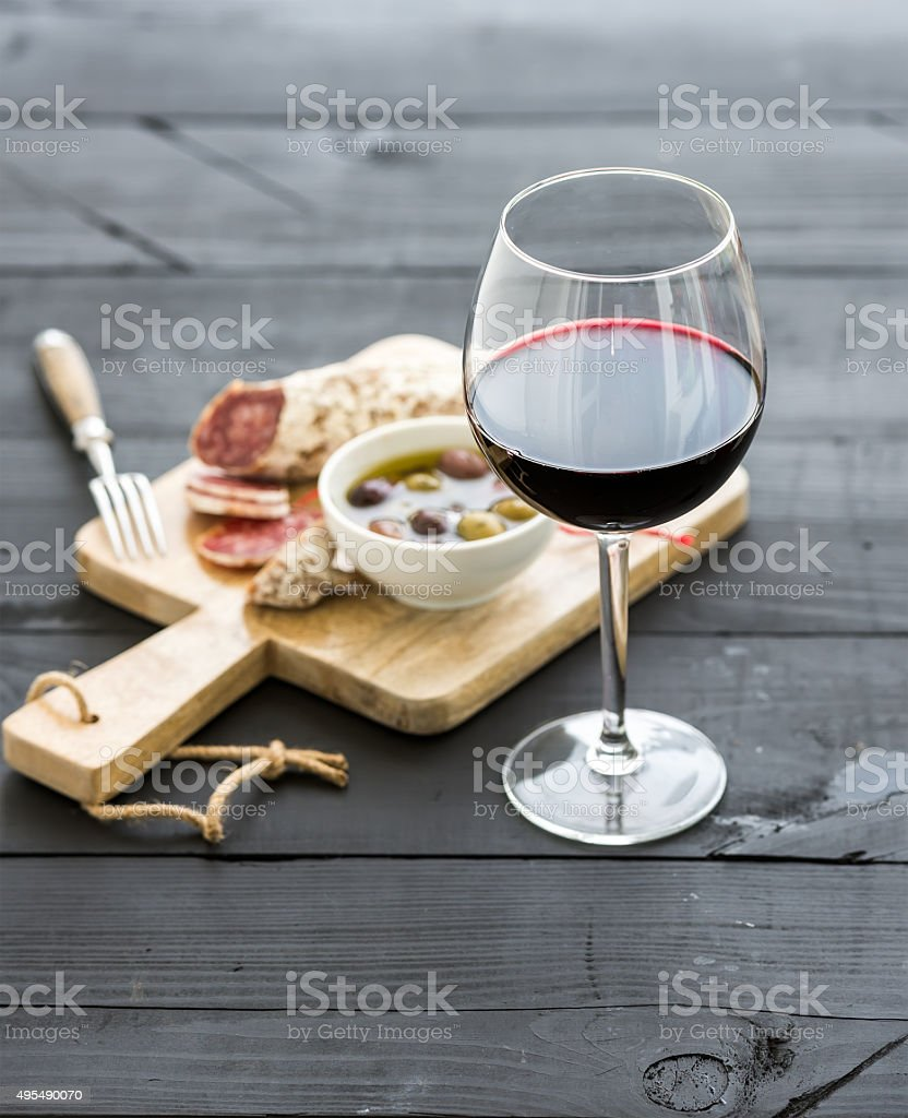 Wine appetizer set. Glass of red wine, French sausage and stock photo