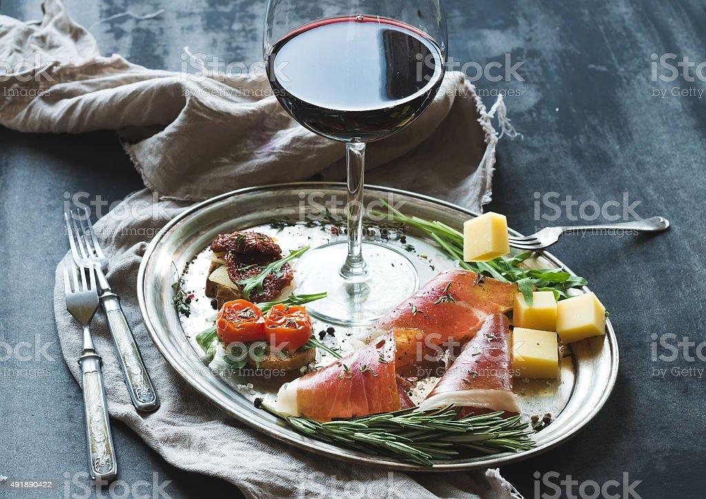 Wine appetizer set. Glass of red wine, vintage dinnerware, brushetta stock photo