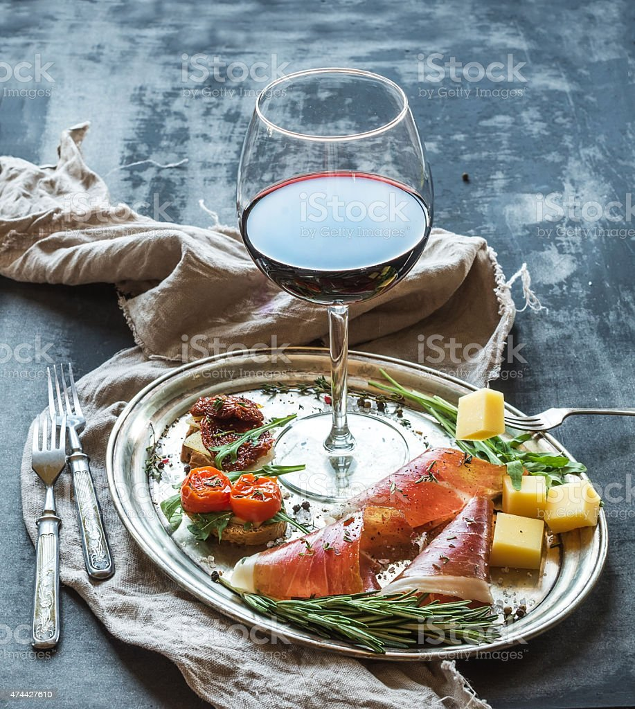 Wine appetizer set. Glass of red wine, vintage stock photo
