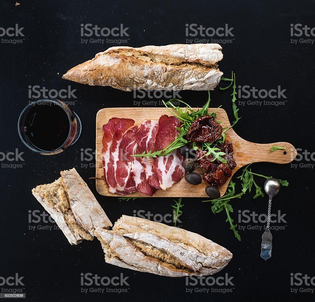Wine appetizer set: vintage dinnerware, french baguette broken into pieces stock photo