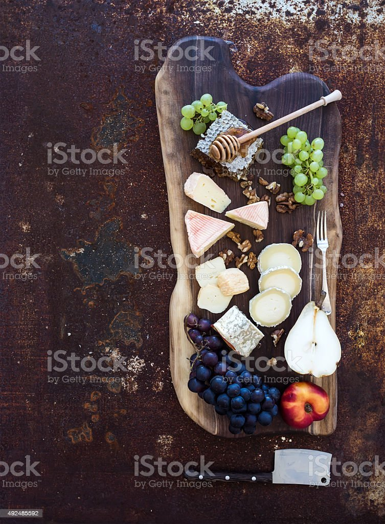 Wine appetizers set: French cheese selection, honeycomb, grapes, peach and stock photo