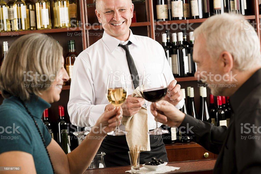 Wine bar senior couple barman pour glass royalty-free stock photo