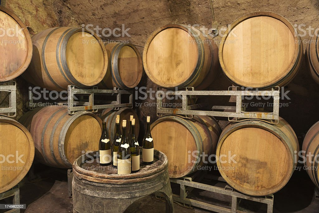 WIne Barrels and Bottles in a French Winery Cellar royalty-free stock photo