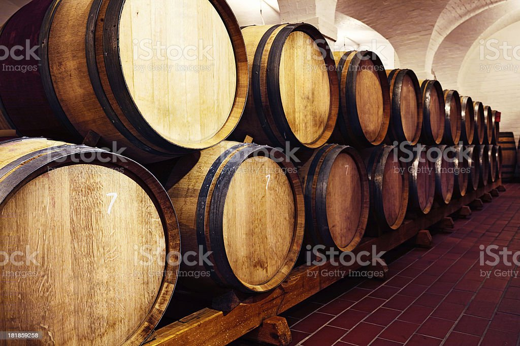 Wine barrels stacked in long row at winery royalty-free stock photo