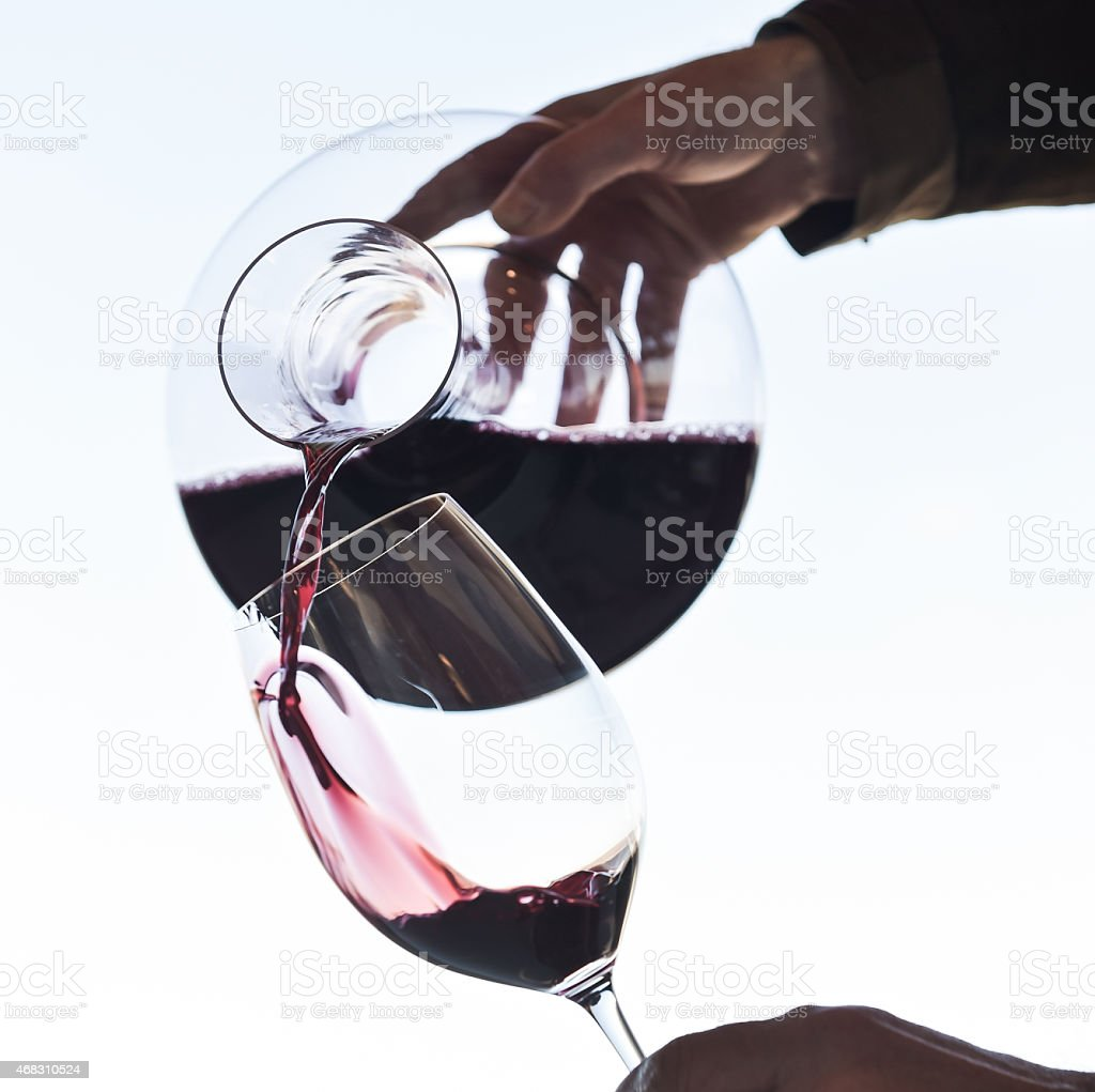 Wine being pored into a wine glass at dinner stock photo