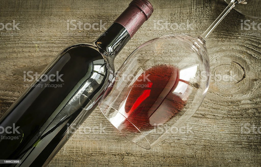 Wine bottle and glass next to each other on wooden counter stock photo