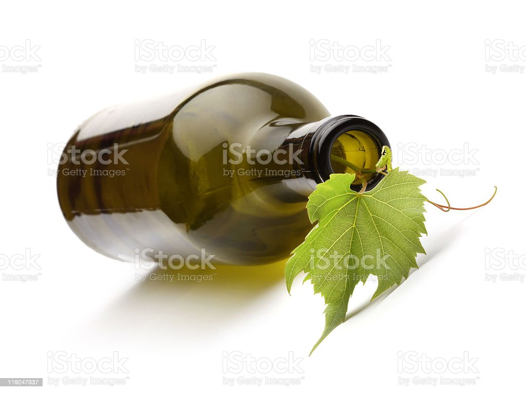 wine bottle and green grape vine stock photo