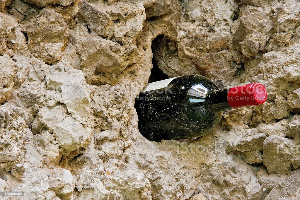 Wine bottle by a rustic old wall royalty-free stock photo