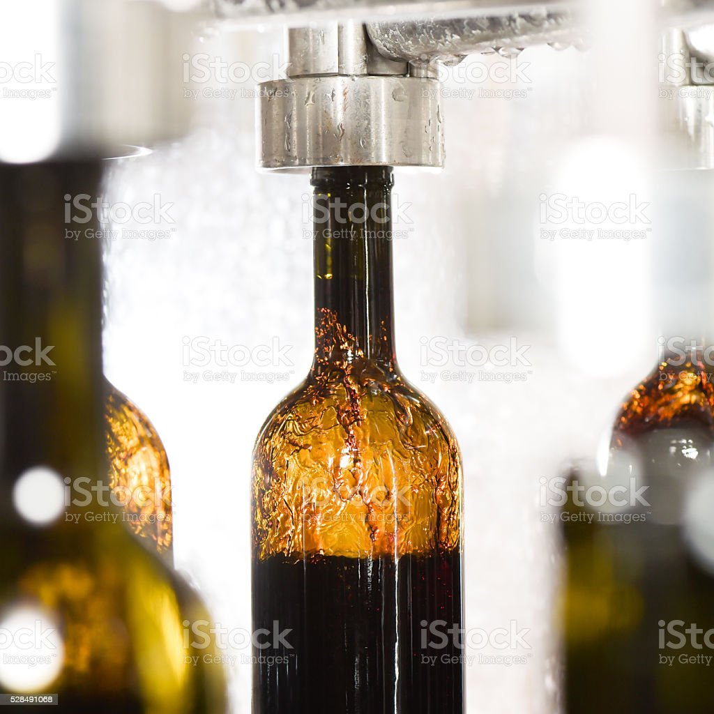 Wine bottle filling along conveyor belt in bottling factory stock photo