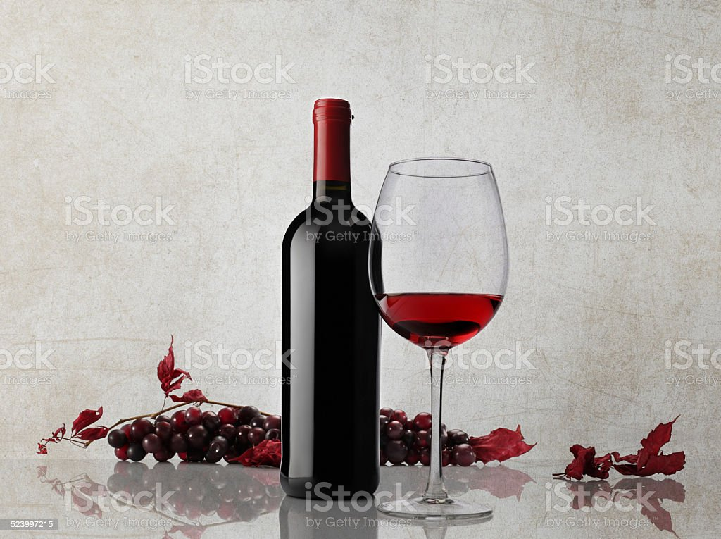 wine bottle glass bunch of grapes on marble background stock photo