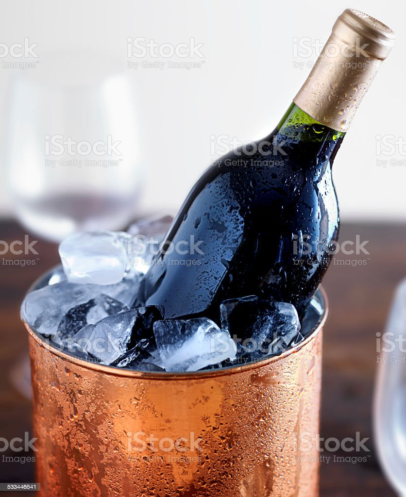 wine bottle in ice bucket with glasses stock photo