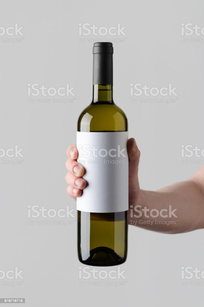 Wine Bottle Mock-Up. Blank Label - Male hands holding a wine bottle on a gray background stock photo