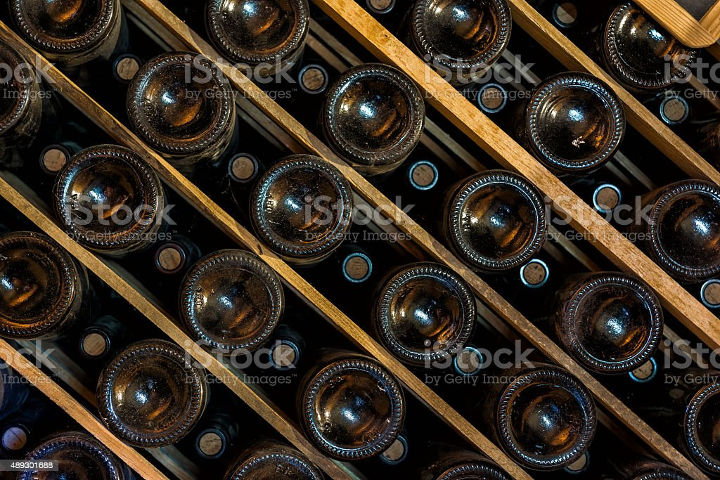 Wine bottles aging in a wine cellar stock photo