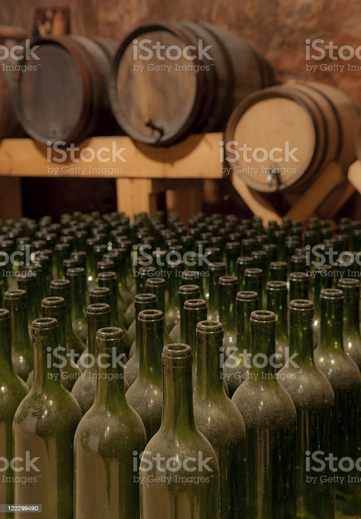 Wine bottles and barrels in cellar royalty-free stock photo