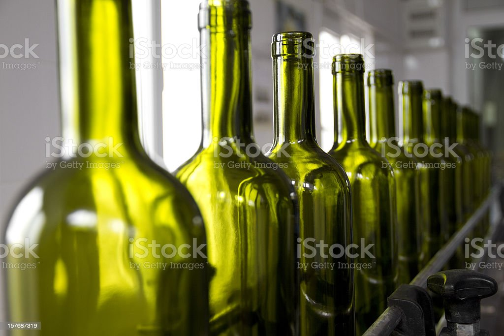 Wine bottles colored green on an assembly line stock photo