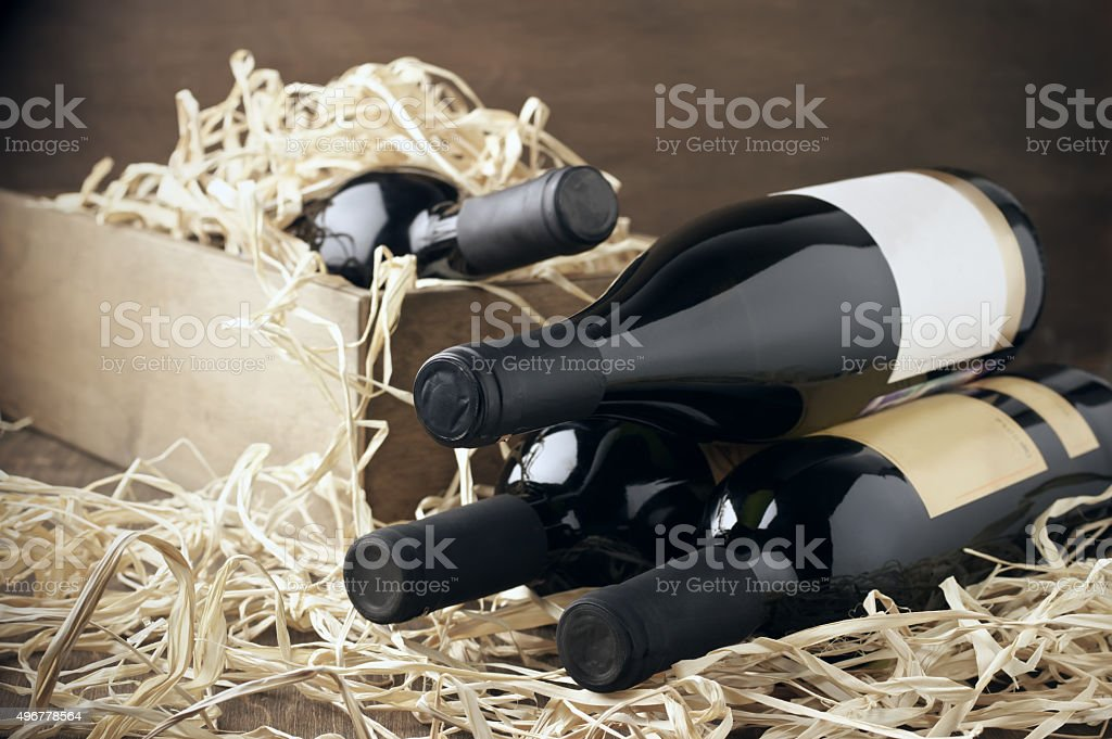 Wine bottles in wooden box and straw stock photo