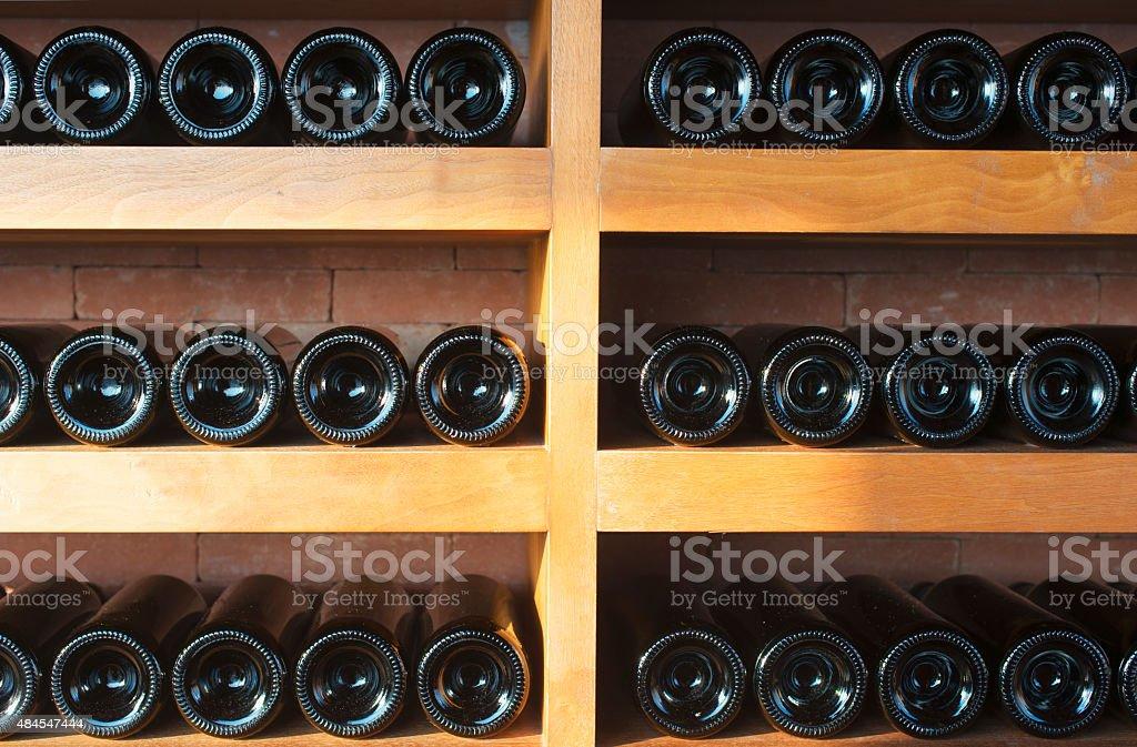 Wine bottles on wooden shelves stock photo