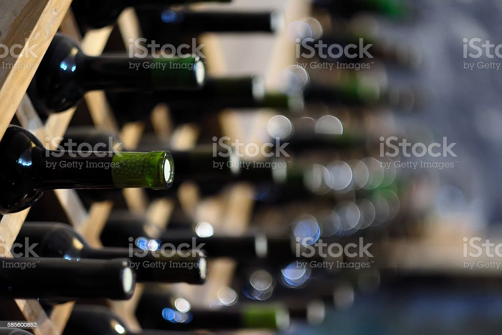 Wine bottles stacked on wooden racks stock photo