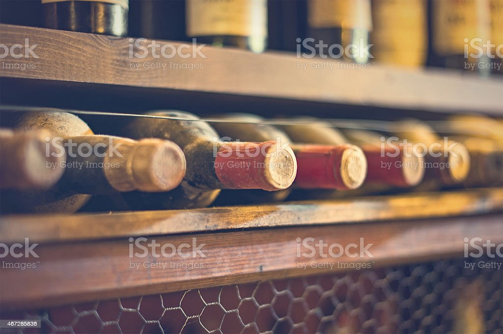 Wine bottles stacked on wooden racks. Vintage effect. stock photo