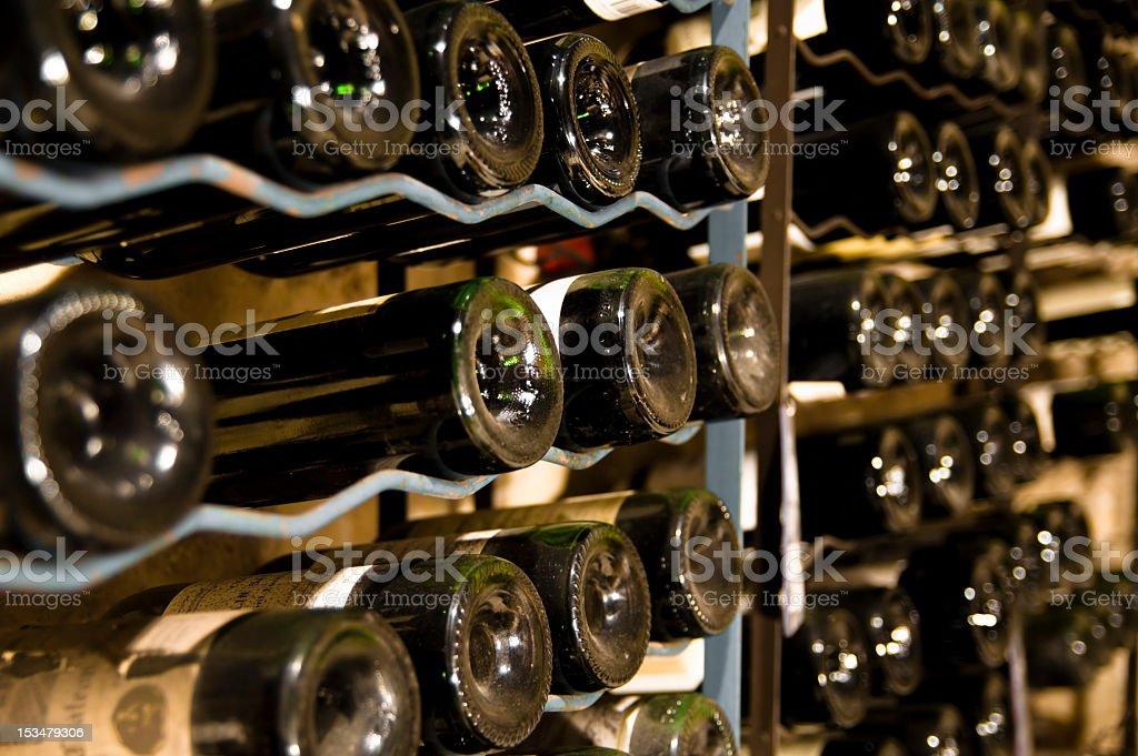 Wine bottles stored on cellar shelves royalty-free stock photo