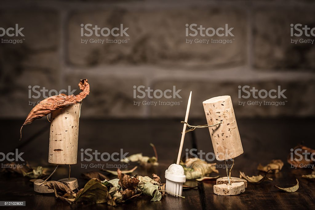 Wine cork figures, Concept two men clean up foliage stock photo