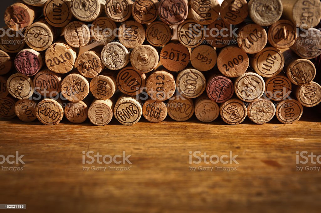 Wine Cork Stoppers with Vintage Years on Rustic Wood Background stock photo