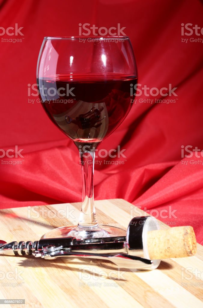 Wine corks, corkscrew and Glass with red wine grapes on wooden table. stock photo