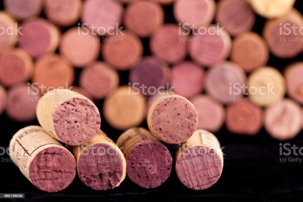 Wine corks on a towel with a stack of more wine corks as a background stock photo