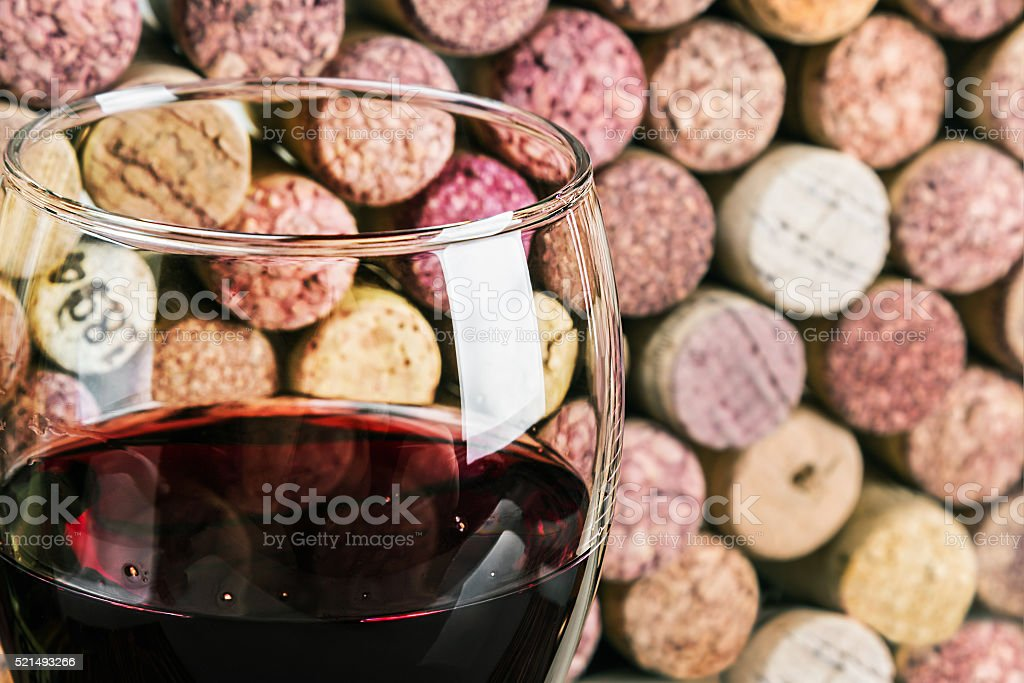 wine corks through a glass of red wine stock photo