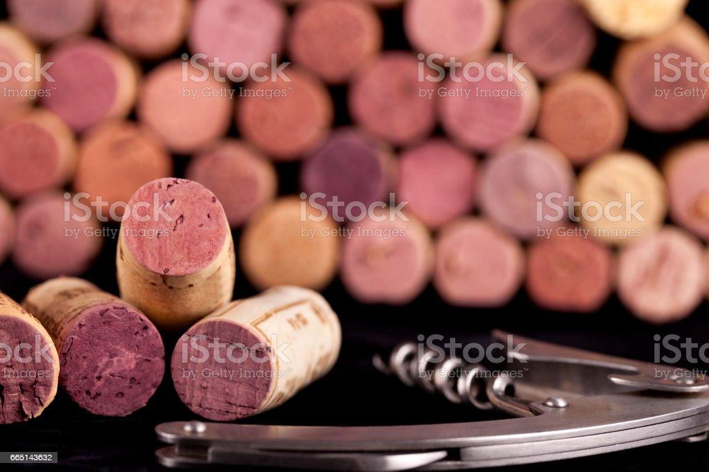 Wine corks with corkscrew sitting on a black towel stock photo