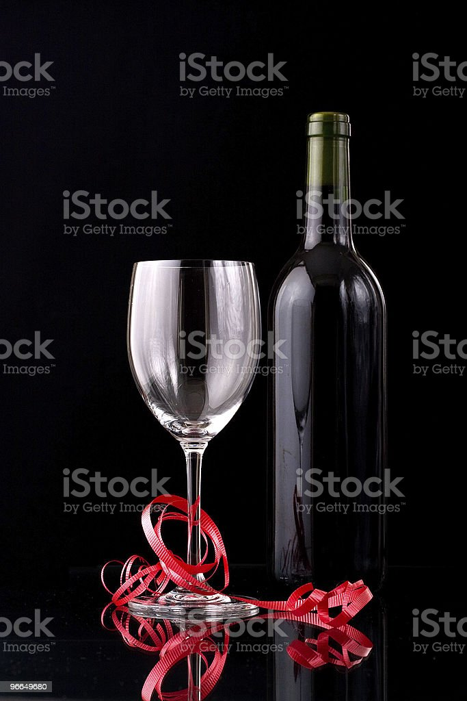 Wine glass and bottle wrapped with red ribbon stock photo