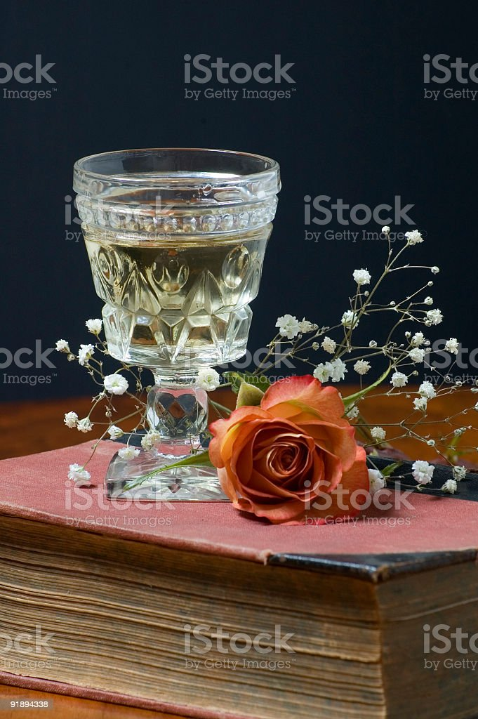 Wine Glass on antique book and table royalty-free stock photo