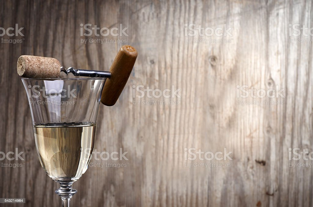Wine glass with corkscrew on wooden background stock photo